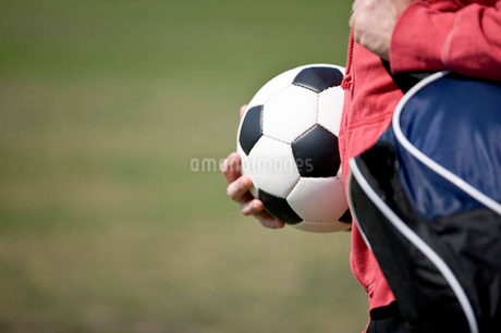 close-up of a young man carrying a football and a sports bagの写真素材 [FYI02125320]