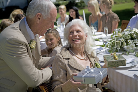 A senior couple with presents at a wedding receptionの写真素材 [FYI02125336]
