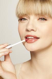 Portrait of young woman applying lip glossの写真素材 [FYI02125340]