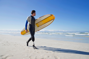 Surfer With Artificial Leg Standing On Beachの写真素材 [FYI02125353]