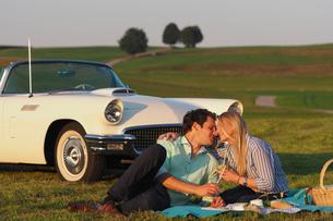 Couple Enjoying Countryside Picnic Next To Classic Carの写真素材 [FYI02125385]