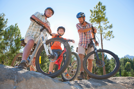 Three generations of men riding mountain bikes in forestの写真素材 [FYI02125397]