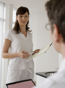 Doctor and nurse going over paper work togetherの写真素材 [FYI02125400]