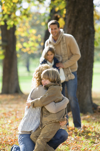 Mother embracing boy in autumn forestの写真素材 [FYI02125409]