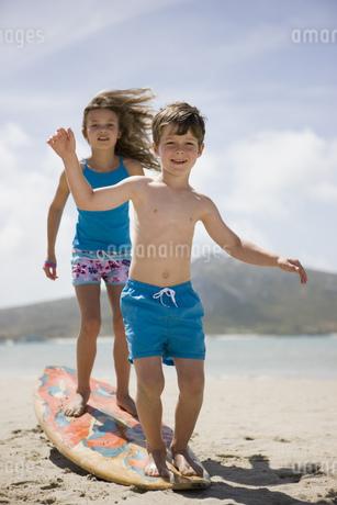 Boy and girl balancing on surfboard on beachの写真素材 [FYI02125416]