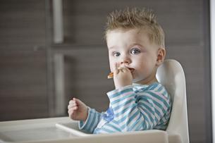 Baby boy eating on high chairの写真素材 [FYI02125423]