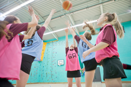 High school students jumping and playing basketball in gym classの写真素材 [FYI02125427]