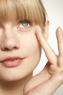 Portrait of young woman applying make up under eyeの写真素材 [FYI02125429]