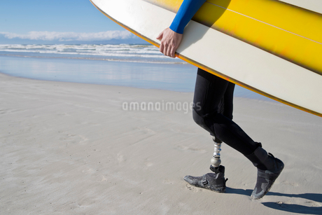 Close Up Of Surfer With Artificial Leg Walking On Beachの写真素材 [FYI02125430]