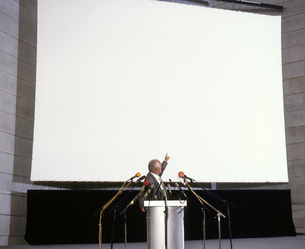 Businessman at podium pointing at large projection screenの写真素材 [FYI02125432]