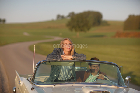 Couple Driving On Country Road In Open Top Classic Carの写真素材 [FYI02125443]