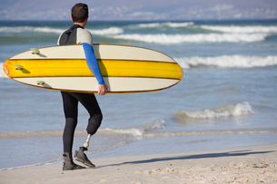 Surfer With Artificial Leg Standing On Beachの写真素材 [FYI02125445]
