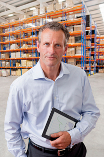 Portrait Of Businessman With Digital Tablet In Warehouseの写真素材 [FYI02125446]