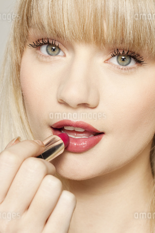 Young woman applying red lipstickの写真素材 [FYI02125452]