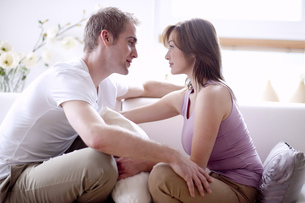 Young couple sitting on sofa, face to faceの写真素材 [FYI02125487]