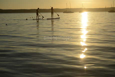 Teenage couple paddle boarding at sunset on Lake Starnberg, Bavaria, Germany, Europeの写真素材 [FYI02125492]