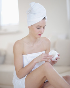 Portrait of young woman in towel putting lotion onの写真素材 [FYI02125541]