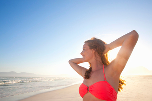 Smiling woman, with arms raised behind head, on sunny beachの写真素材 [FYI02125559]