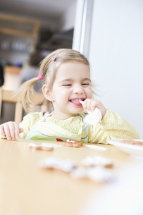 Girl licking icing bag in kitchenの写真素材 [FYI02125568]