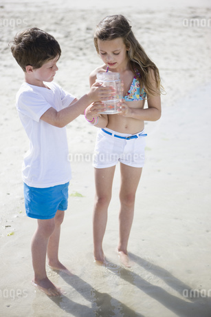 Boy and girl looking in jar ion beachの写真素材 [FYI02125580]