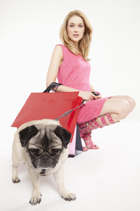 Young woman in pink dress with pet pug, portraitの写真素材 [FYI02125594]