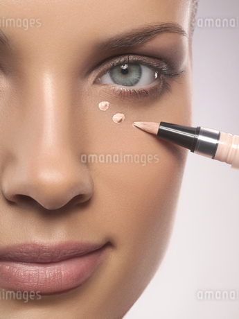 Close-up portrait of young woman applying make-up foundation, studio shotの写真素材 [FYI02125610]