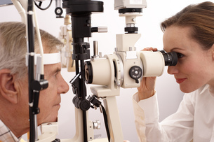 Optician performing eye exam on manの写真素材 [FYI02125627]