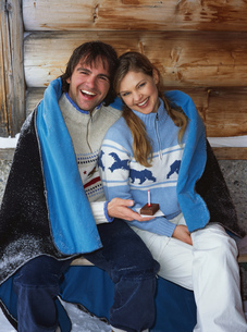 Couple wrapped in blanket with cake and candleの写真素材 [FYI02125641]