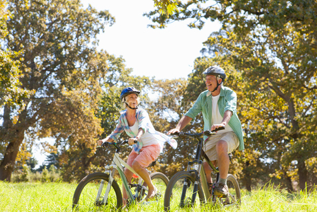 Older couple riding mountain bikes in rural fieldの写真素材 [FYI02125646]