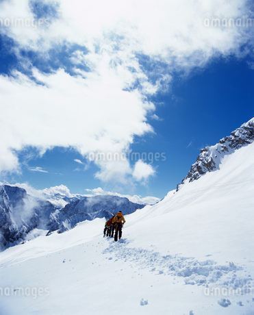 Rear view of hikers on snowy mountainの写真素材 [FYI02125665]