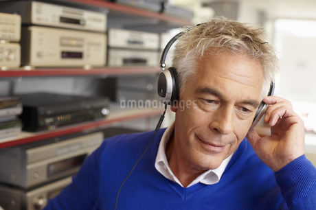 A mature man wearing a pair of headphones, listening to musicの写真素材 [FYI02125671]
