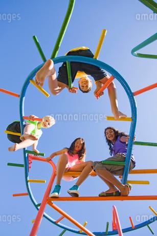 Smiling children sitting on monkey bars at playgroundの写真素材 [FYI02125679]
