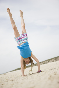 Young girl performing handstand on beachの写真素材 [FYI02125682]