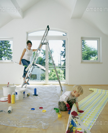 Portrait of a young woman on a ladder as her son fingerpaints on a roll of wallpaperの写真素材 [FYI02125692]