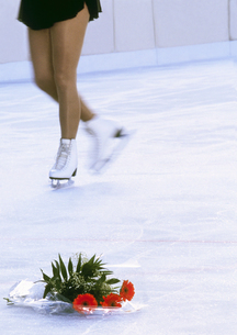 Blurred view of a woman skating with white ice skates with a bouquet of flowers on the iceの写真素材 [FYI02125732]