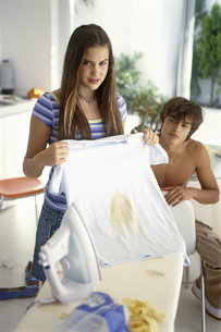 Teenage girl holding up shirt with iron burn as teenage boy looks from behindの写真素材 [FYI02125746]