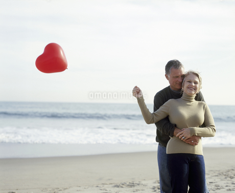 View of a middle aged man embracing his wife as she holds a heart-shaped balloonの写真素材 [FYI02125756]
