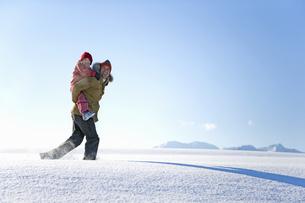 Man carrying daughter through snowの写真素材 [FYI02125805]