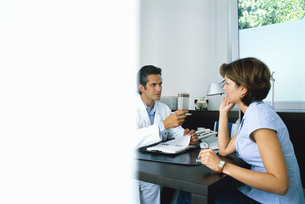Male doctor talking to a female patientの写真素材 [FYI02125813]