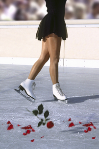 View of a female ice skater skating on ice littered with flower petalsの写真素材 [FYI02125820]