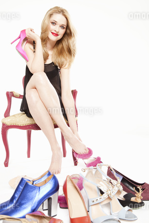 Young woman in negligee trying on shoes, portraitの写真素材 [FYI02125850]