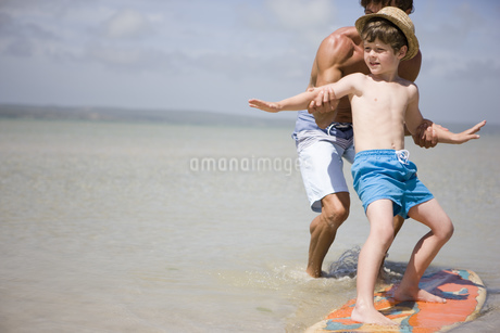 father teaching son how to surf in seaの写真素材 [FYI02125891]