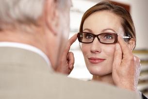 Optician adjusting eyeglasses on patient in officeの写真素材 [FYI02125898]