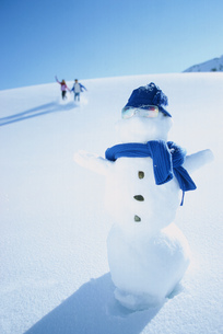 Couple in distance approaching snowmanの写真素材 [FYI02125972]