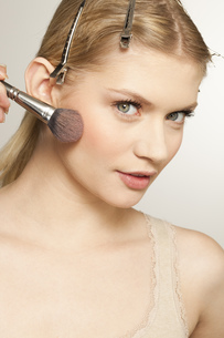 Young woman applying make up with brush, portraitの写真素材 [FYI02125973]