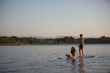 Teenage couple on paddleboard on Lake Starberg, Bavaria, Germany, Europeの写真素材 [FYI02126003]