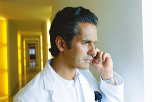 Doctor talking on his cell phoneの写真素材 [FYI02126010]