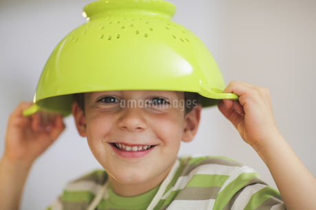 A young boy with a green colander on his headの写真素材 [FYI02126038]