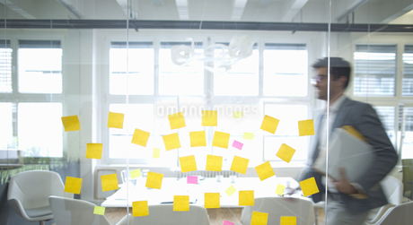 Businessman Walks Past Glass Wall Covered In Sticky Notesの写真素材 [FYI02126040]