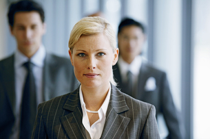 View of a businesswoman with businessmen out of focusの写真素材 [FYI02126041]